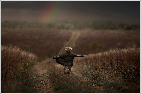 Child running down path in grassy field